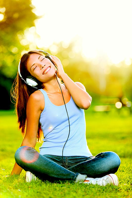Photo of woman smiling while listening on headphones for the blog post If you gave up on meditating – this is for YOU by Dr. Susan Spicer, founder of Brainwave Technologies