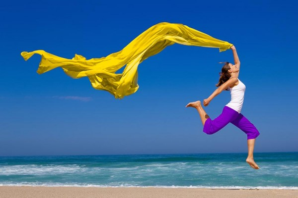 Photo of woman jumping for joy on beach for the blog post How can I find more joy in my life by Dr. Susan Spicer, founder of Brainwave Technologies