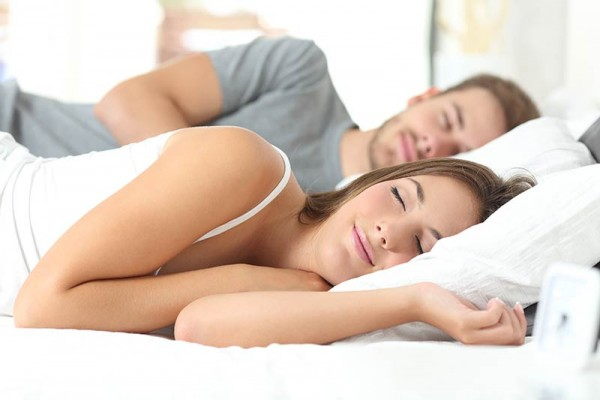 "Couple sleeping peacefully in bed illustrating the blog post ""12 Simple Techniques to Improve Your Sleep"""