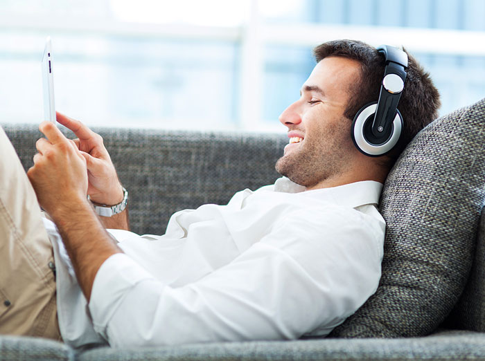 Photo of man lying on couch listening to brainwave therapy productivity audio on headphones