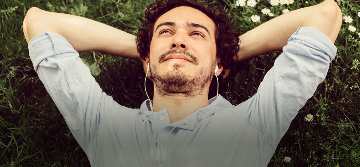 Photo of man lying on the grass listening to brainwave therapy meditation audio on earbuds