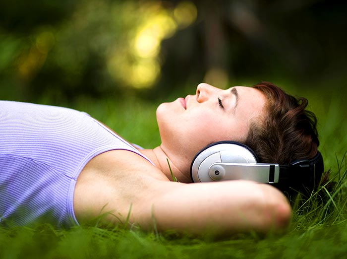 Photo of woman lying on the grass listening to brainwave therapy relaxation audio on her headphones