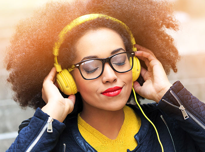 Photo of woman listening on headphones and smiling